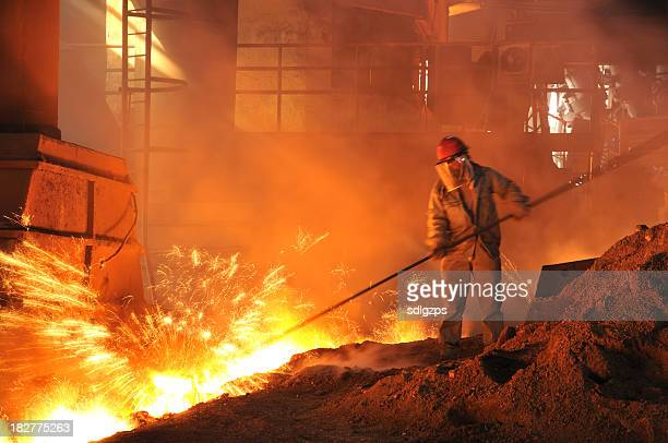 Man in a mask performing iron-making duties in a fiery pit