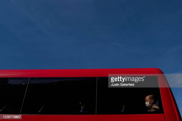Man in a mask sits at the back of a bus in Kentish Town on May 19, 2020 in London, England. The British government has started easing the lockdown it...