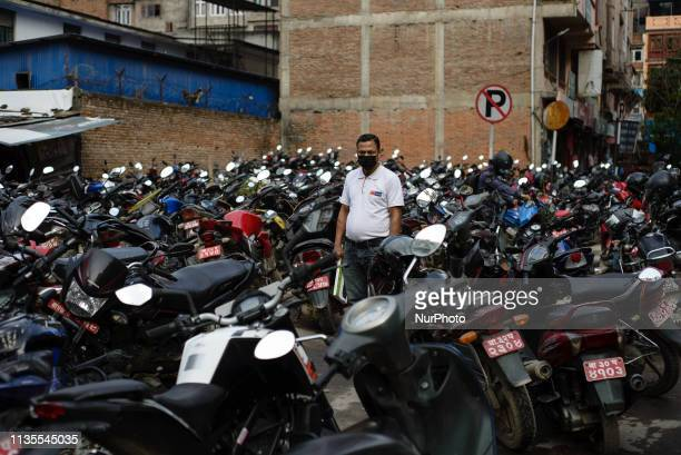 A man in a mask stands among parked motorcycles in Thamel district Kathmandu Nepal on April 7 2019