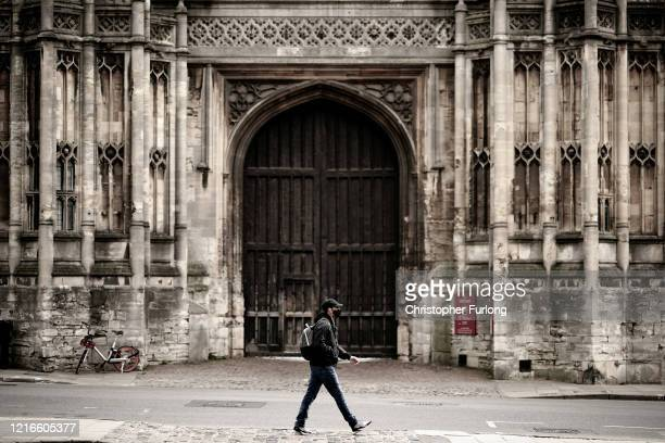 A man in a mask walks past Christ Church after university students have been sent home and the tourists are staying away during the Coronavirus...
