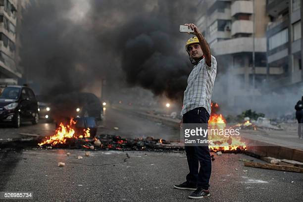 A man in a motorbike helmet taks a 'selfie' in front of burning tires and garbage on the main airport road near downtown Beirut as residents...