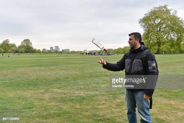 Man in a park playing with vodka bottle