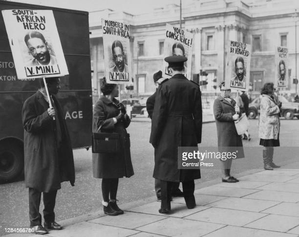 Man in a peaked cap stands before anti-apartheid demonstrators holding placards in memory of South African ANC activist Vuyisile Mini, one of the...