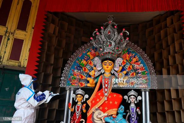 Man in a personal protective equipment suit sanitises an idol of the Hindu goddess Durga ahead of the upcoming 'Durga Puja' festival, in Kolkata on...