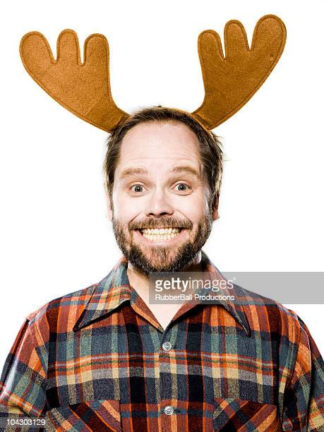 man in a plaid shirt wearing antlers - rentier stock-fotos und bilder