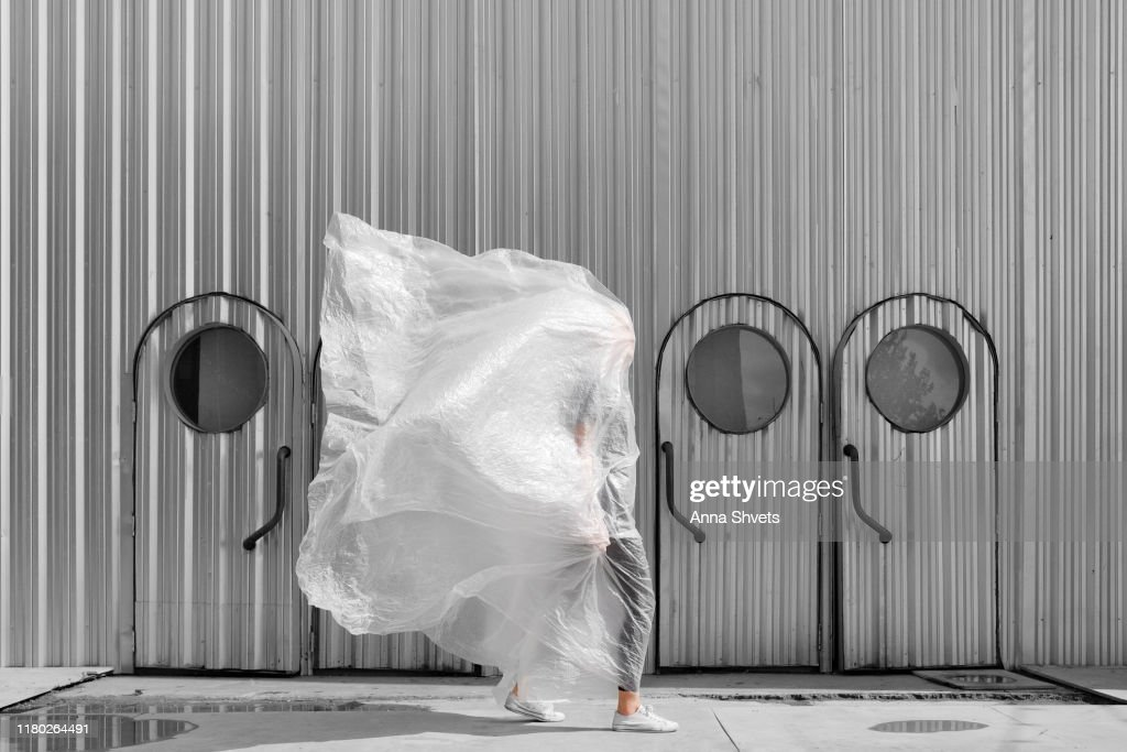 A man in a plastic on the background of a silver tin building : Stock Photo