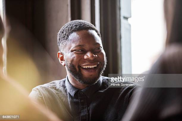 man in a pub laughing with friends - selective focus stock pictures, royalty-free photos & images