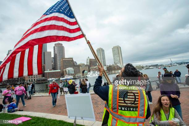 Man in a QAnon vest unfurls a US Flag as demonstrators gather to protest a mandatory flu vaccine order for children and to protest government...
