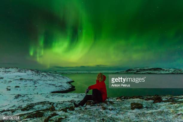 man in a red jacket on a background of the northern lights - finland stock pictures, royalty-free photos & images