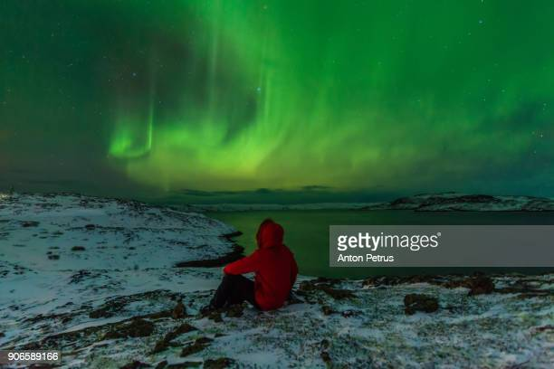 Man in a red jacket on a background of the Northern Lights