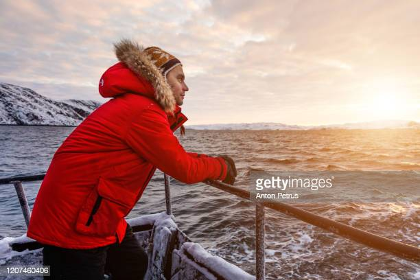 man in a red jacket on board a ship in the winter in the arctic - winter coat stock pictures, royalty-free photos & images