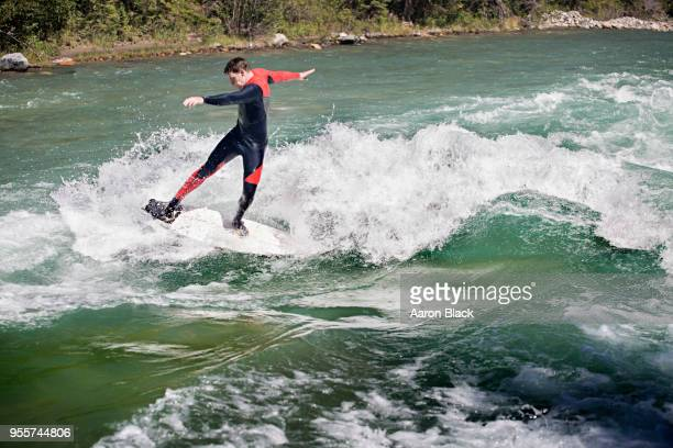 man in a red wetsuit standing on surfboard surfing a greenish wave in the middle of a river. - kananaskis stock-fotos und bilder