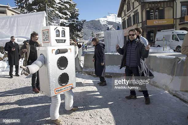 A man in a robot costume with a writing reading in 'We work for you' is seen at the entrance of Congress Hall where the World Economic Forum is held...