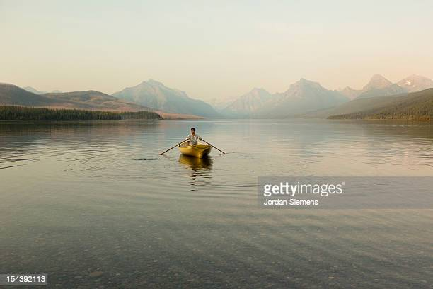 a man in a row boat. - rowing boat stock pictures, royalty-free photos & images