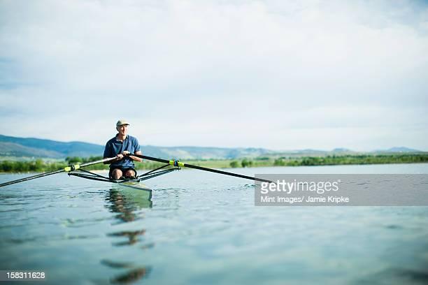 a man in a rowing boat using the oars. - alleen seniore mannen stockfoto's en -beelden