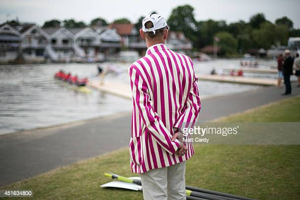 A man in a rowing race blazer watches as boat crews return to the jetty at the end of the day's racing at the Henley Royal Regatta on July 2 2014 in...