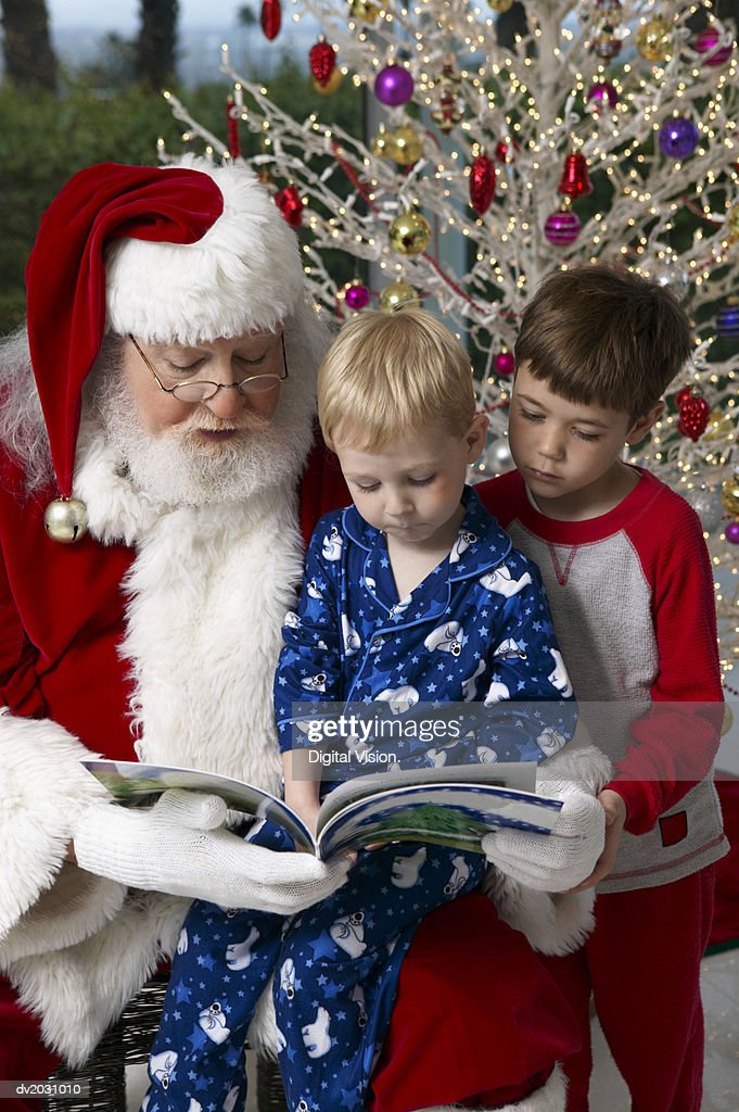 Man in a Santa Outfit Reads to Two Young Boys From a Picture Book : Stock Photo