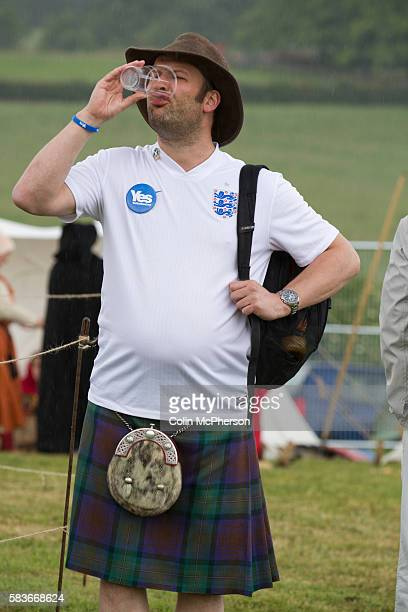 A man in a Scottish kilt wearing an England football shirt and drinking a beer during events at Bannockburn Live at Bannockburn Stirlingshire The...