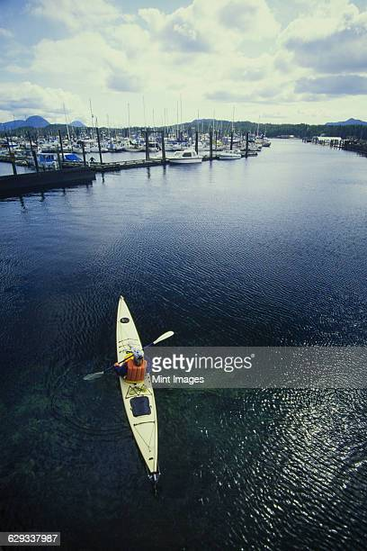 a man in a sea kayak in the creek or estuary at ketchikan. - estuary stock pictures, royalty-free photos & images