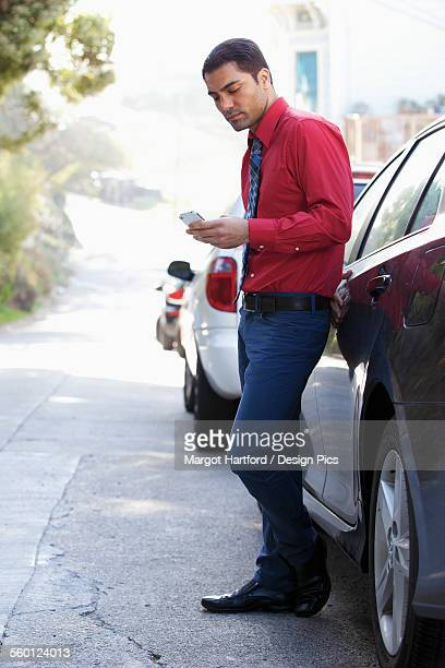 A man in a shirt and tie standing by his car using his cell phone