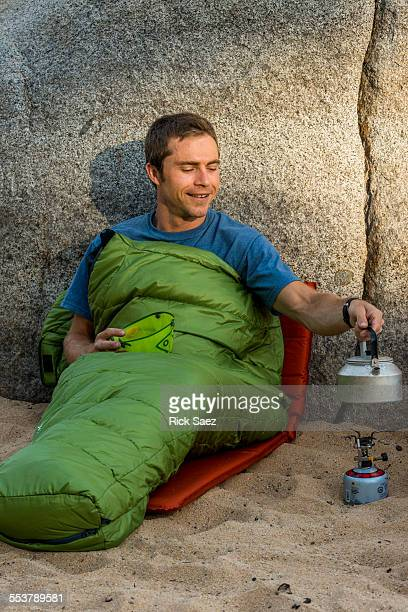 Man in a sleeping bag heating water