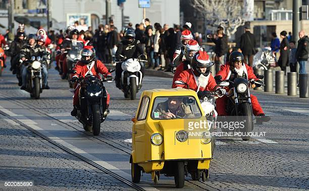 A man in a small car drives ahead of bikers dressed as Santa Claus who parade on the Vieux Port in Marseille southern France on December 20 2015 as...