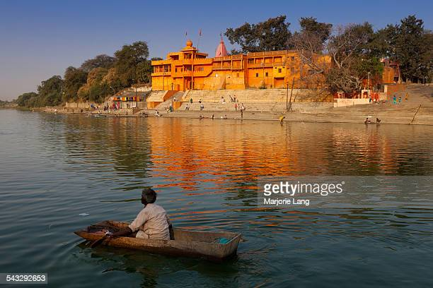 Man in a small roaming boat on the holy Shipra or Kshipra river from Ramghat with a view on a colorful Hindu temple in Ujjain Madhya Pradesh India