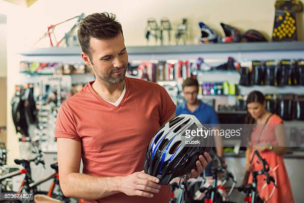 Man in a sports store buying bike helmet