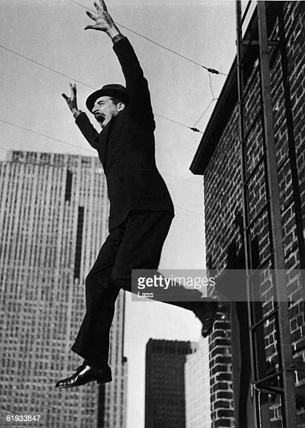 A man in a suit and hat attempts to commit suicide by jumping from a fire escape circa 1935