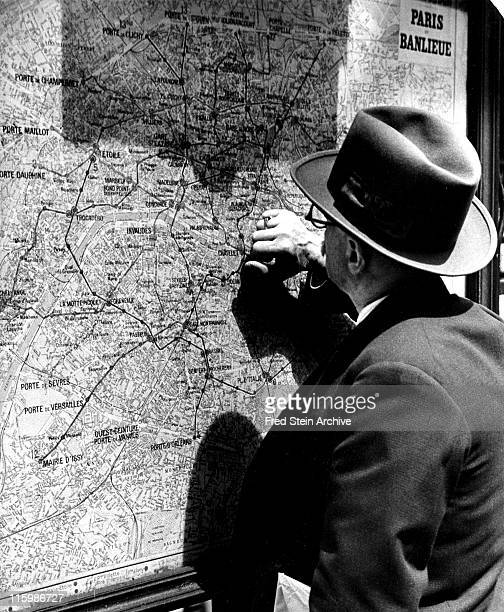 A man in a suit and hat reads a wallmounted map of the Metro Paris France 1935