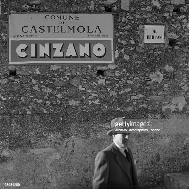 A man in a suit and hat stands before a wall where a sign advertises Cinzanobrand liquor Castelmola Sicily Italy 1954