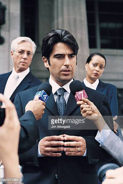 Man in a Suit Being Interview by TV Reporters