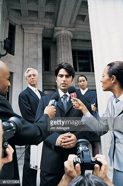 Man in a Suit Being Interviewed by Journalists