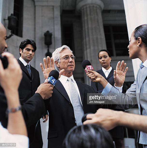 Man in a Suit Being Interviewed by TV Reporters With Microphones