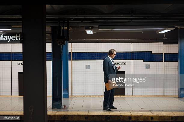 Man in a suit checks his cell phone while waiting for a train on the Broadway-Lafayette platform of the New York City subway.