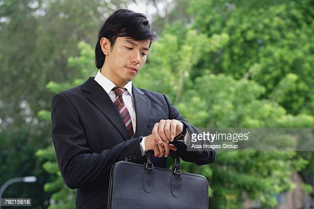 A man in a suit checks his watch for the time