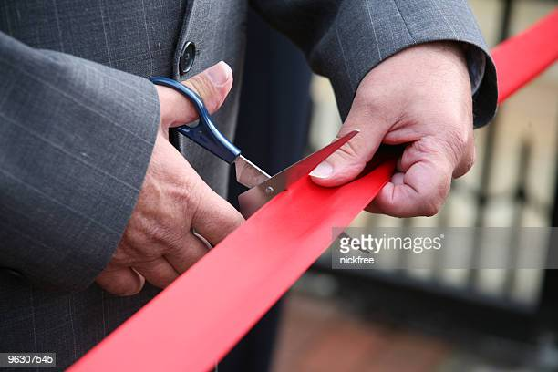 Man in a suit cutting a red ribbon