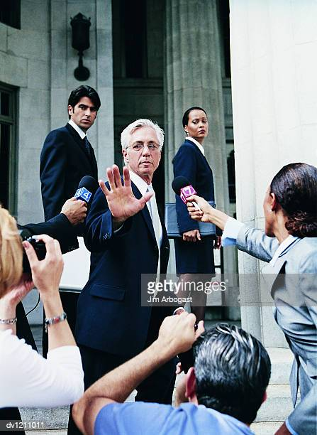 Man in a Suit Escaping From Cameramen and TV Reporters by a Building