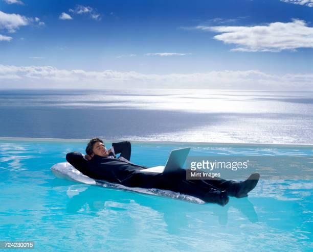 a man in a suit on a lilo in a swimming pool, a laptop on his lap. - 水に浮かぶ ストックフォトと画像