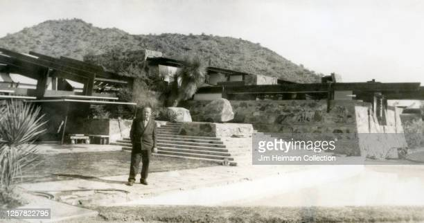 A man in a suit poses for a picture in front of Frank Lloyd Wright's winter home Taliesan West circa 1948