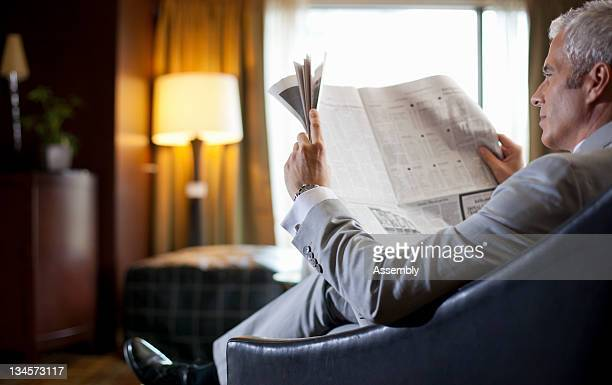 A man in a suit reads a newspaper.