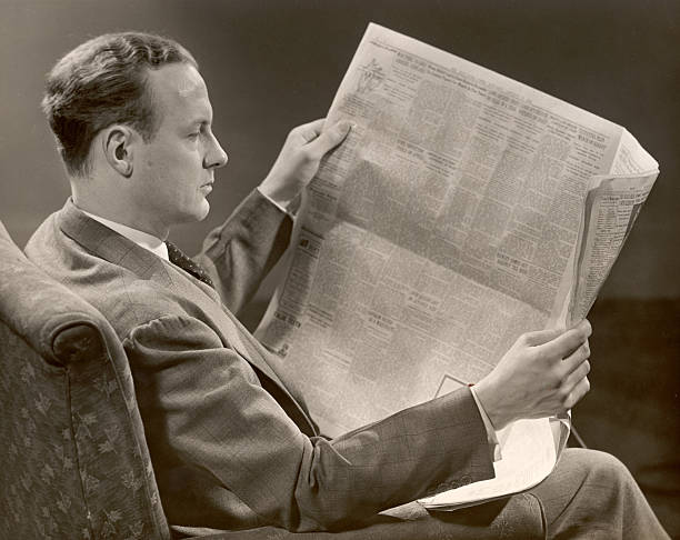 A man in a suit sits in a chair and reads a newspaper...