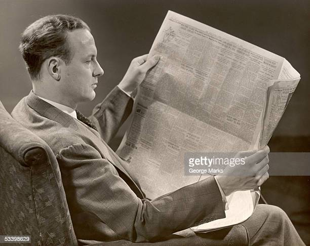 A man in a suit sits in a chair and reads a newspaper which he holds in his hands New York state 1930s