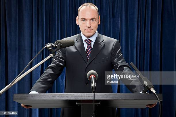 a man in a suit standing at a lectern - conferenza stampa foto e immagini stock