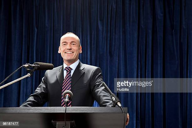 a man in a suit standing at a lectern - politician stock pictures, royalty-free photos & images