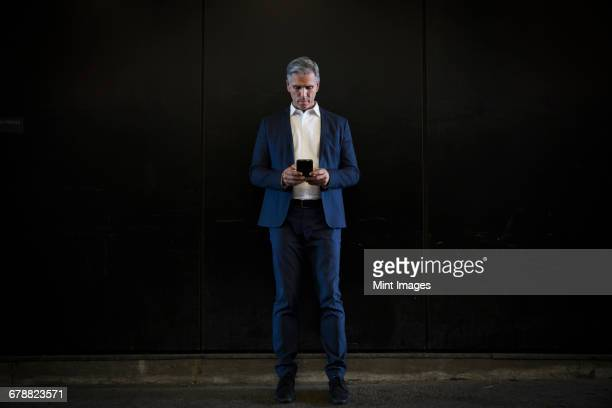 a man in a suit standing in shadow on a city street, looking at his smart phone, texting or searching for information on line.  - open collar stock photos and pictures