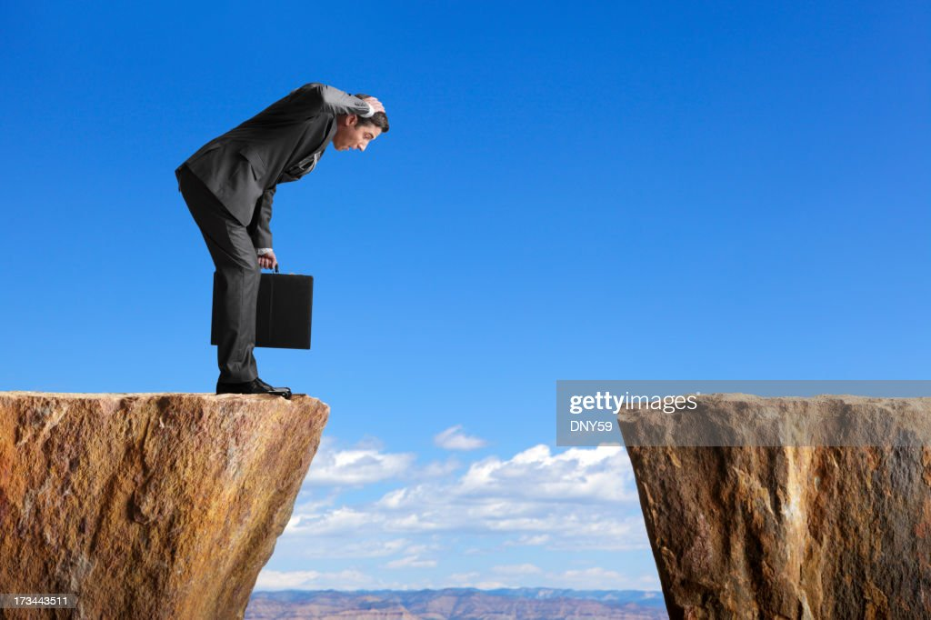 Man in a suit stares at space between two ledges : Stock Photo