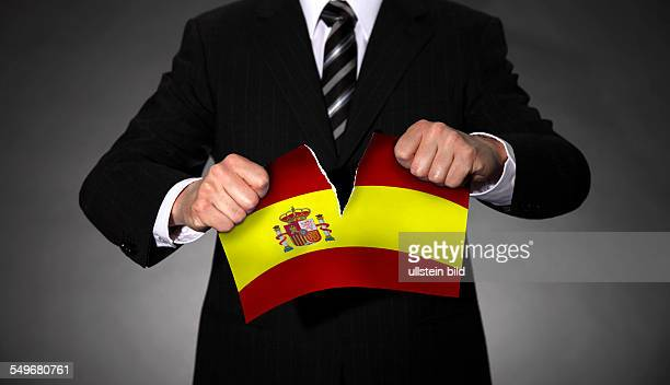 Man in a suit tearing apart the national flag of Spain