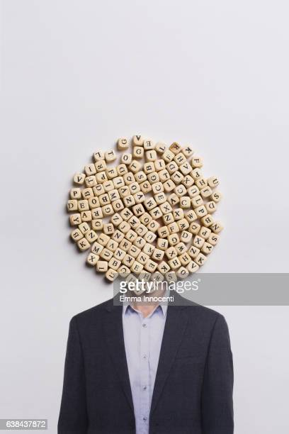 Man in a suit with head covered in letters