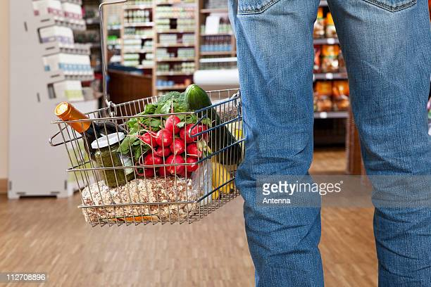A man in a supermarket with a full shopping basket, low section